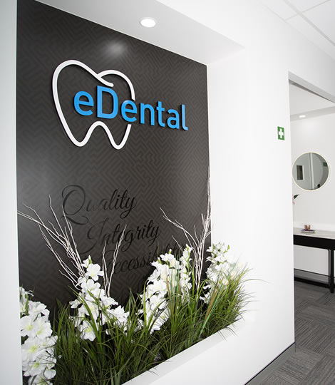 Wall with the logo of the eDental Perth with flowers and plants below it and that is considered as one of the general dentistry of eDental Perth.