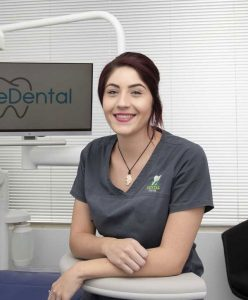 Lady smiling, leaning on one of the dental chair and wearing a gray uniform with the logo of eDental Perth and is one of the dental support team.