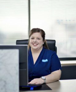 Woman smiling, sitting on a black frontdesk chair and wearing a blue uniform with the logo of eDental Perth and is one of the dental support team.