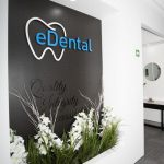 Wall with the logo of the eDental Perth with flowers and plants below it and that is considered as one of the dental clinic of eDental Perth.