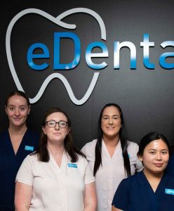 Women wearing blue and white uniform standing behind the logo of eDental Perth and are one of the dental support team.