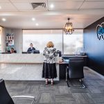 Black wall with the logo of the eDental Perth and along with the frontdesk tellers, chairs and a customer which is considered as one of the dental clinic of eDental Perth.