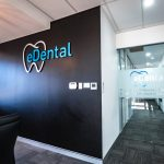 A black wall across the hallway inside eDental Perth office with a logo on it.
