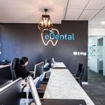 Staff on the front desk of eDental Perth office waiting for clients coming in. There are chairs reserved for clients and there's a wall painted in black with eDental's logo on it
