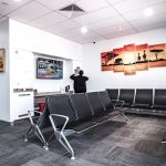 eDental Perth clinic reception/waiting area. There are chairs reserved for clients and there are decorative paintings hanging on the wall.