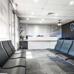 Black wall with the logo of the eDental Perth and along with the frontdesk and chairs which is considered as one of the dental clinic of eDental Perth.