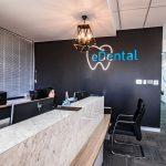 Black wall with the logo of the eDental Perth and along with the frontdesk tellers and chairs which is considered as one of the dental clinic of eDental Perth.