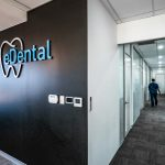 Black wall with the logo of the eDental Perth with the hallway-view of the offices and that is considered as one of the dental clinic of eDental Perth.
