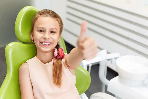 Child sitting on a green chair, wearing a flesh colored dress and making a thumbs-up and having the child dental benefits schedule which is one of the services of eDental Perth.