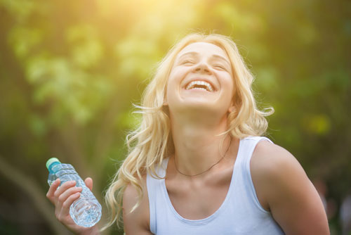 Woman smiling and holding a bottled water, which describes the