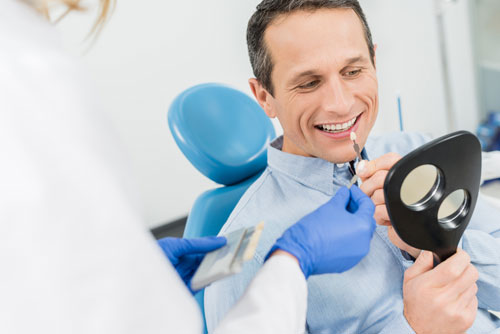 "Dental nurse assisting a man smiling and looking on a mirror, which describes the ""type of dental restoration"" blog."