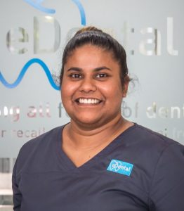 A smiling female staff of eDental Perth wearing a uniform that has a logo on her left chest. She's standing on a glass wall that has eDental's logo.