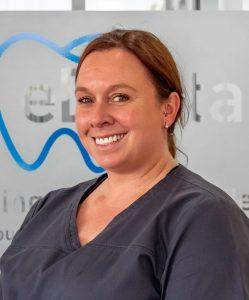 Female nurse from eDental Perth wearing grey uniform, namely Sheralyn.