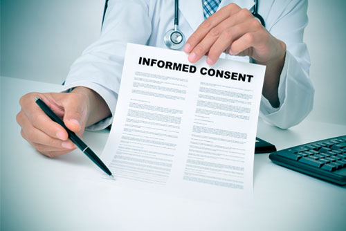 "A doctor holding a pen and a piece of paper ""Informed Consent"", and as the featured image of ""medical consent"" blog."