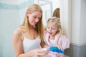 A mother and her daughter pouring a mouthwash on a small cup, as the featured image of