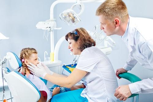 2 dental nurses looking on a girl's teeth that represents the