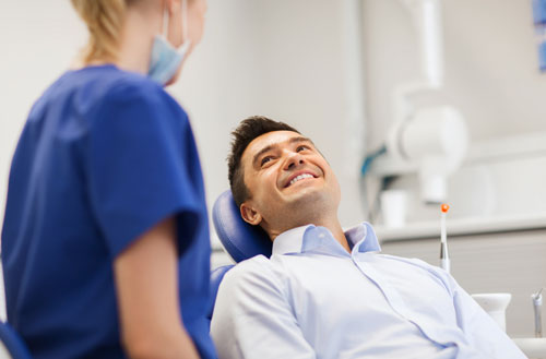 Smiling male patient facing a dental nurse and that represents the