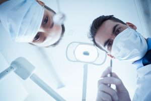Low angle view of 2 dentists in surgical masks holding dental tools, and as the header image of