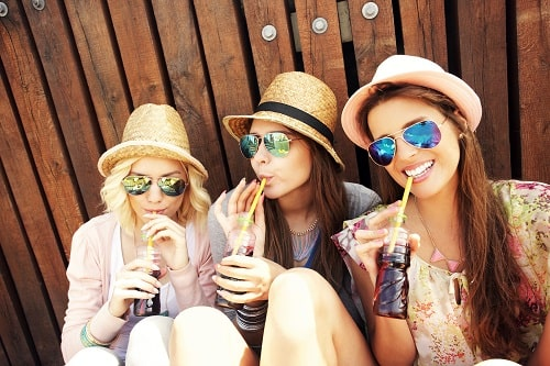 3 girls sitting and sipping a soft drinks, and that represents the