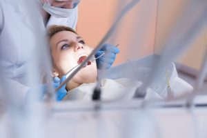 Dentist looking and checking the teeth of his female patient and as the header image of