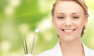 Woman dentist smiling and holding her dentist's tools and as the header image of