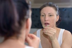 Woman putting on her mouthguard and that represents the