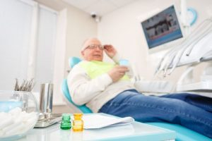Male patient sitting on a dental chair and that represents the